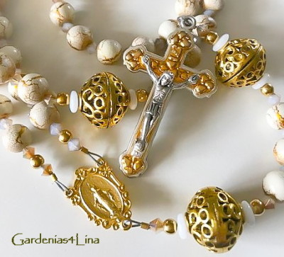 Golden and White limited edition rosary focused on the story of Our lady of the Snows